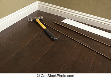 Hammer, Laminate Flooring and New Baseboard Molding Abstract.