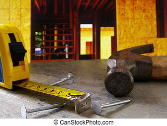 Hammer, nails, and tape measure with new home construction...