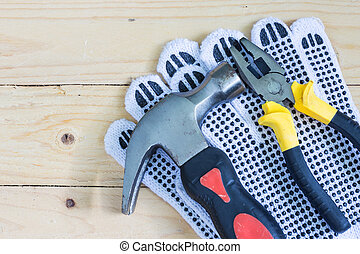 hammer pliers and gloves on wooden background