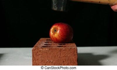Hammer smashing apple over bricks in slow motion