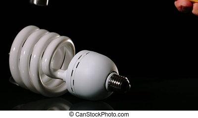 Hammer smashing light bulb on black surface - Hammer...