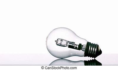 Hammer smashing light bulb on white background in slow...