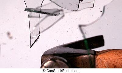 Hammer smashing through pane of glass in slow motion
