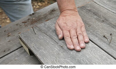 hammering nail - closeup of a man hammering a used nail into...