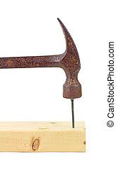 Hammering nail into wood stud
