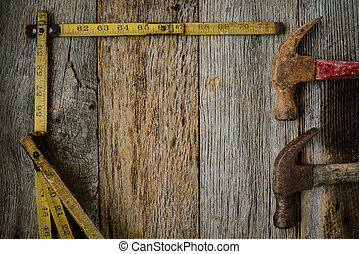 Hammers and Measuring Tape on Rustic Old Wood Background