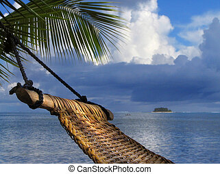 Hammock on a palm tree on a tropical beach. Concept of relaxation and vacation.