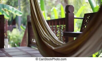 Hammock on the terrace of a villa in the jungle on blurred bokeh from plant.