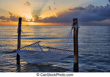 Hammock over the sea at sunset