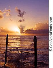 Hammock over water at sunset vertical