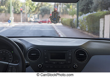 Hamsa hand amulet hanging in the car