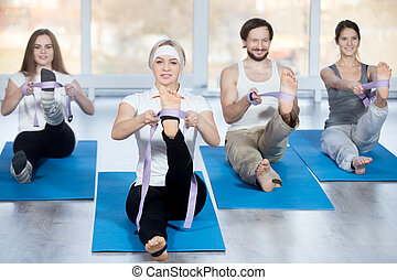 Fitness, stretching practice, group of four beautiful happy fit young people working out in sports club, doing hamstring stretch exercises with props belts on blue mats in class