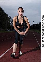 Hamstring stretch female athlete on running track