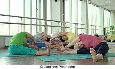 Hamstring Stretching - Five women performing hamstring...