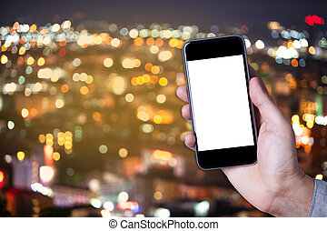 Hand a part of man holding smartphone empty screen with bokeh background of city.