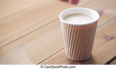 hand adding and stirring sugar in cup of coffee