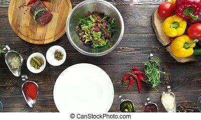 Hand adding mustard to salad. Food preparation, wooden...