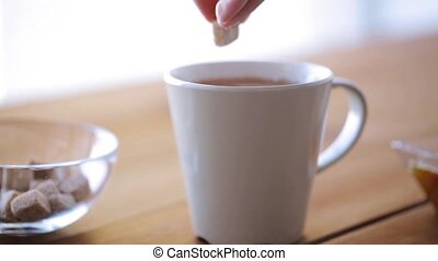 hand adding sugar to cup of tea or coffee