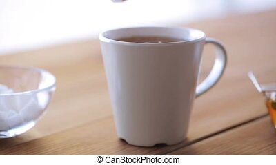 hand adding sugar to cup of tea or coffee - unhealthy eating...