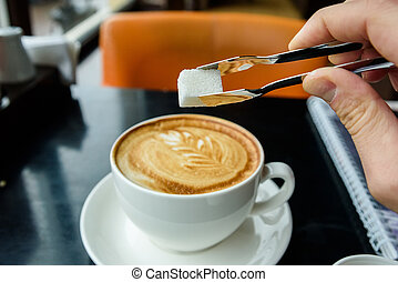 Hand adds lump of sugar to coffee