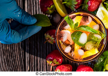 Hand adds mint to homemade srawberry mojito