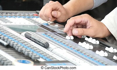 Hand Adjusting Audio Mixer - Man using a sound mixing desk...