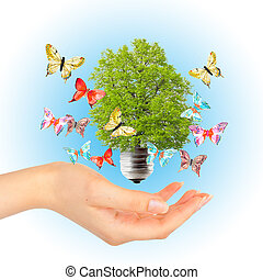 Hand and green tree in light bulb
