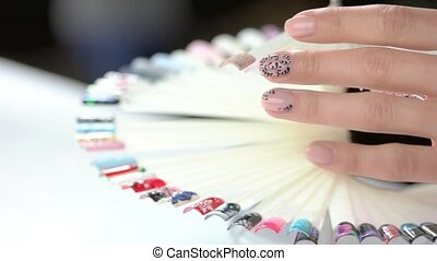 Hand and nail design samples. Woman in nail salon choosing...