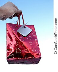 hand and present - hand holding gift bag