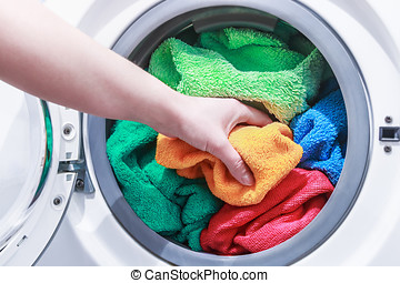 hand and puts the laundry into the washing machine