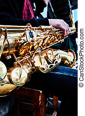 hand and saxophone details in a band, music show