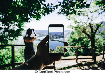 Hand and smartphone taking photo of beautiful landscape at the Monte Barro with a girl on the foreground. Lomardy. Italy.