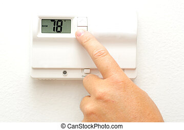 Hand and thermostat - A hand turning down the thermostat for...