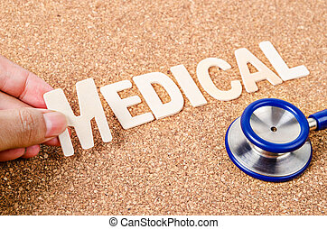 Hand arrange wood letters as medical word with stethoscope.