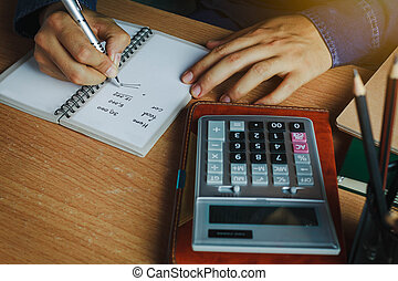 hand Asian man calculate finances and accounting for monthly expenses / charges or cost on notebook with accessories in home office room.Idea to save / security money and control income or recipe.