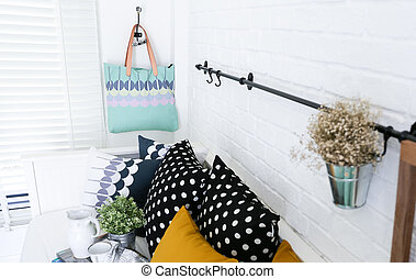 Hand bag hung on the white brick wall with colorful pillows