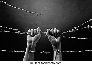 hand behind barbed wirewith dark background