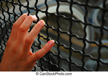 hand behind bars - girls hand holding bars