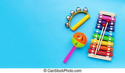 Hand bells musical instrument for ringing with colorful xylophone and baby rattle on blue background.