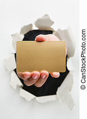 Hand breakthrough wall holding empty golden card - one of ...