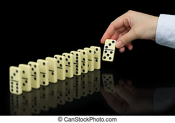 Hand builds a line of dominoes on black background