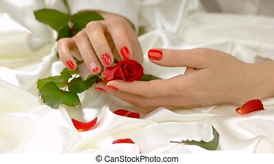 Hand caress rose, slow motion. Beautiful female hand with...