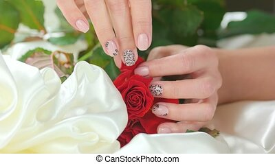 Hand caress roses on white silk. Young woman hand with...