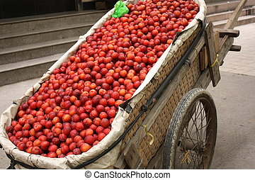 Hand cart full of plums in asian street