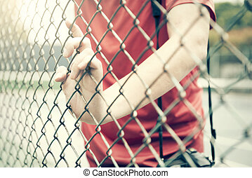Hand catching mesh cage.. The prisoner want freedom.