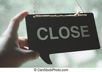 Hand changing closed sign board through the glass of door