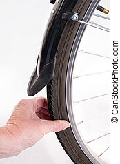 Hand checks the amount of air in a bicycle wheel - studio...