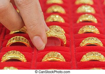hand choosing gold rings in gold Showcase