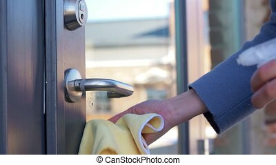 hand cleaning door handle with detergent and rag - hygiene, ...
