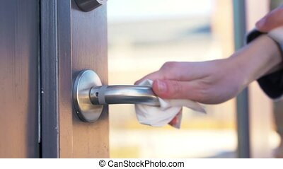 hand cleaning door handle with disinfectant spray - hygiene...
